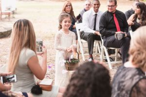 Flower girl walking down the aisle during a DIY boho wedding in Central Florida captured by top Orlando photography team
