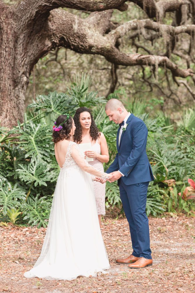 Bride and groom exchange vows under a beautiful tree during their outdoor wedding ceremony in Kissimmee photographed by top Orlando wedding photographer