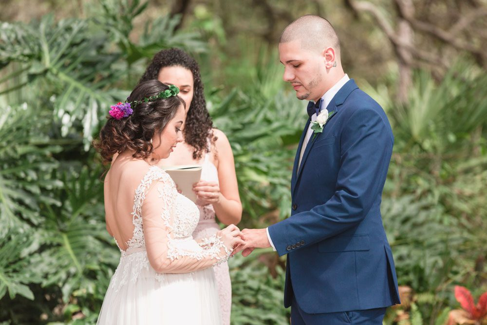 Top Orlando wedding photographer captured bride and groom exchanging rings under a tree during their outdoor wedding ceremony in Kissimmee Florida