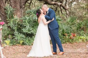 Top Orlando wedding photographer captures bride and groom sharing their first kiss under a tree during their outdoor wedding ceremony in Orlando Florida