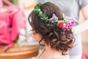 Bride shows off her curly up-do hairstyle and her floral crown for her intimate Orlando wedding