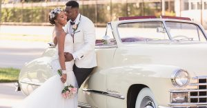 Couples poses in front of an antique vintage car during their Orlando wedding at Lake Eola captured by top wedding photographer and videographer