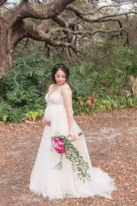 Portrait of the beautiful pregnant bride under a tree after an outdoor backyard wedding ceremony in Kissimmee, Florida captured by top Central Florida photography team