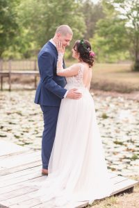 Sweet photo of the newlyweds on a dock during their romantic intimate backyard wedding day in Kissimmee Florida captured by top Orlando wedding photography team