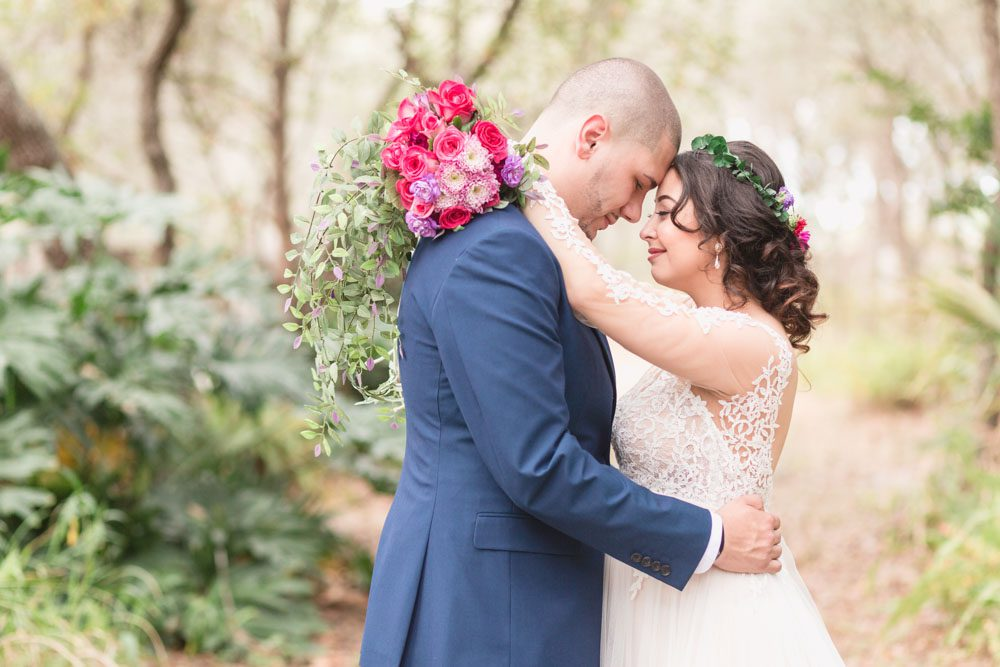 Top Orlando wedding photographer captures romantic photo of the bride and groom in the forest during their intimate DIY wedding in Kissimmee