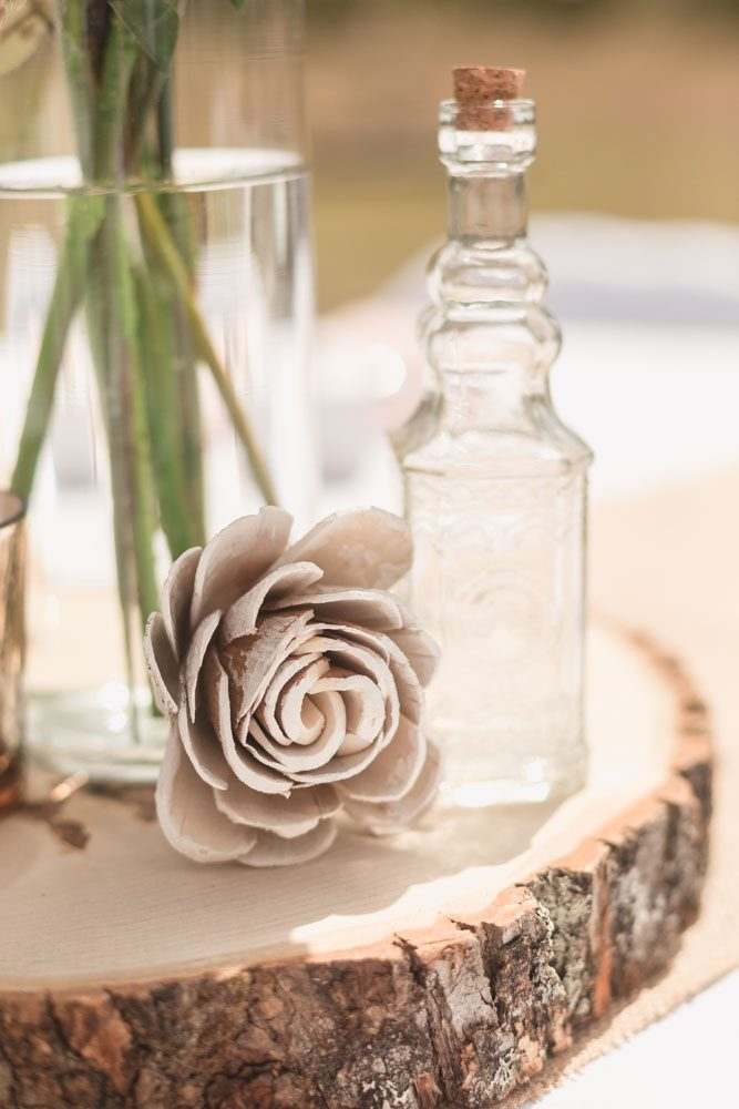 DIY handmade details for a rustic boho chic with wooden details and glass bottles for a beautiful centerpiece