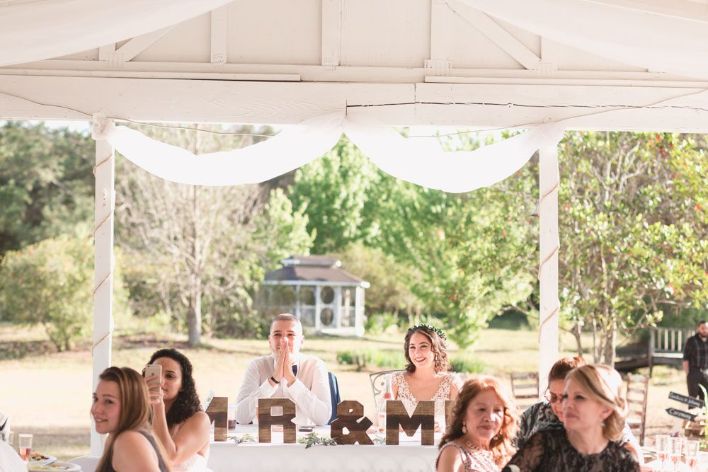Bride and groom receive speeches from behind their sweetheart table during a romantic outdoor wedding reception in Orlando captured by top Central Florida wedding photographer