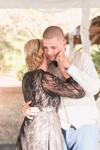 Groom shares an emotional first dance with his mom during their outdoor wedding reception in a backyard in Kissimmee