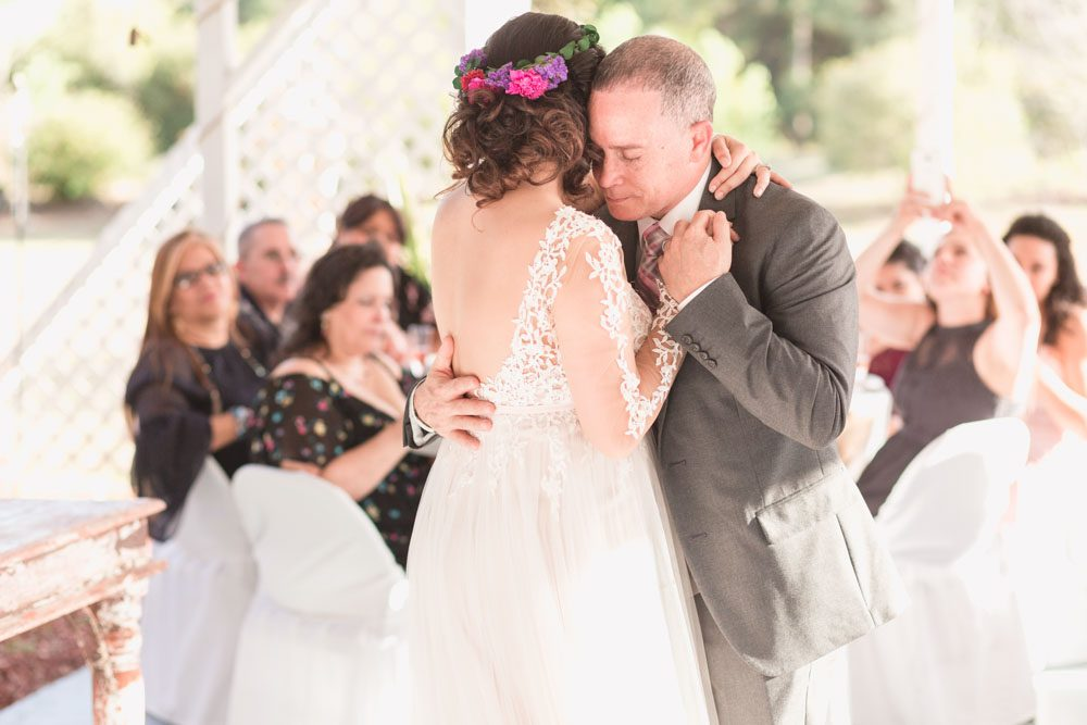 Bride shares an emotional first dance with her dad during their outdoor wedding reception in a backyard in Kissimmee, Florida