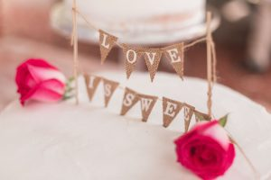 Adorable cake topper that reads 'love is sweet' in burlap fabric for a rustic chic DIY wedding in Kissimmee