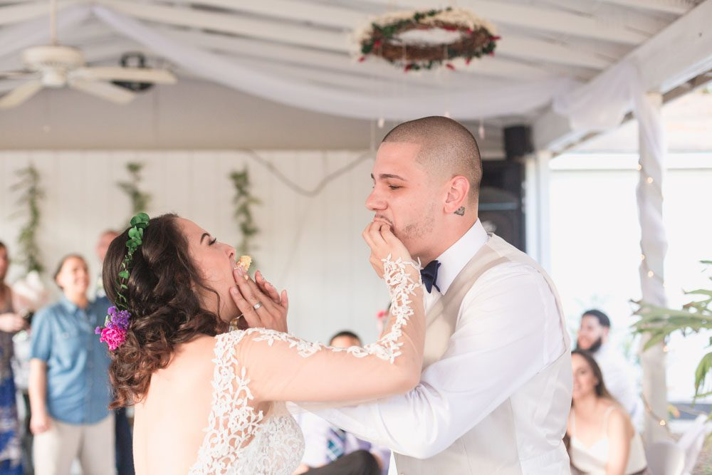Bride and groom cut the cake and smash it in each others face during a fun outdoor wedding in Orlando, Florida