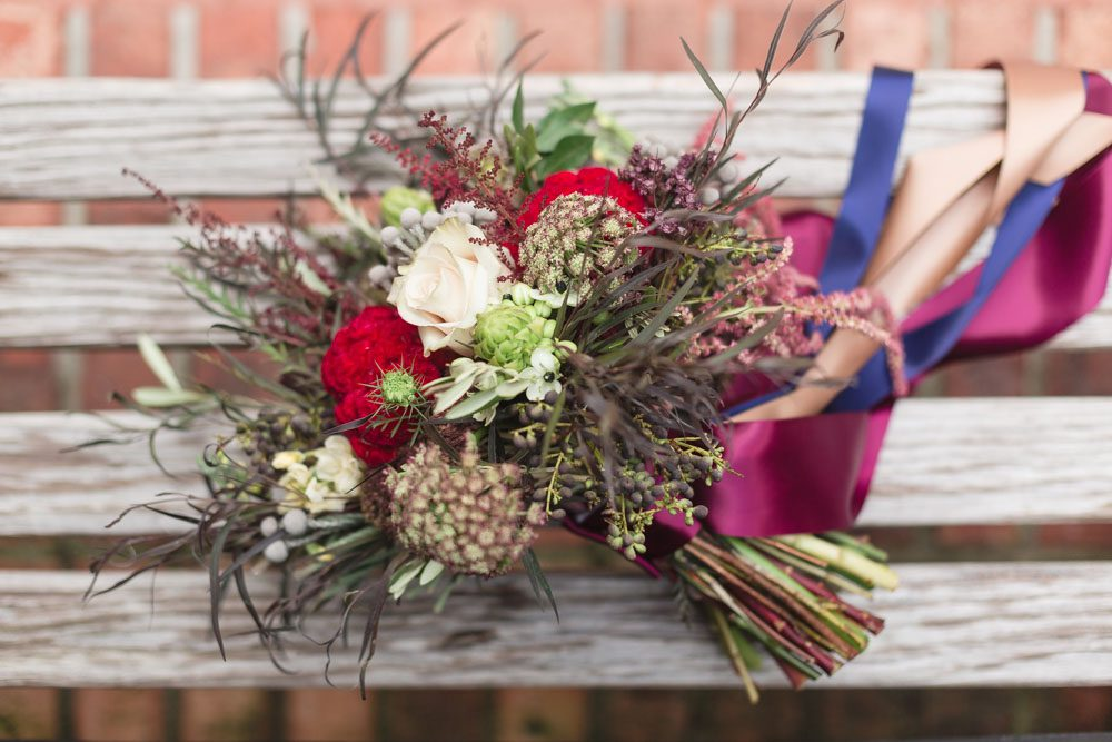 Wild burgundy and white bouquet with ribbons and greenery by top Orlando florist