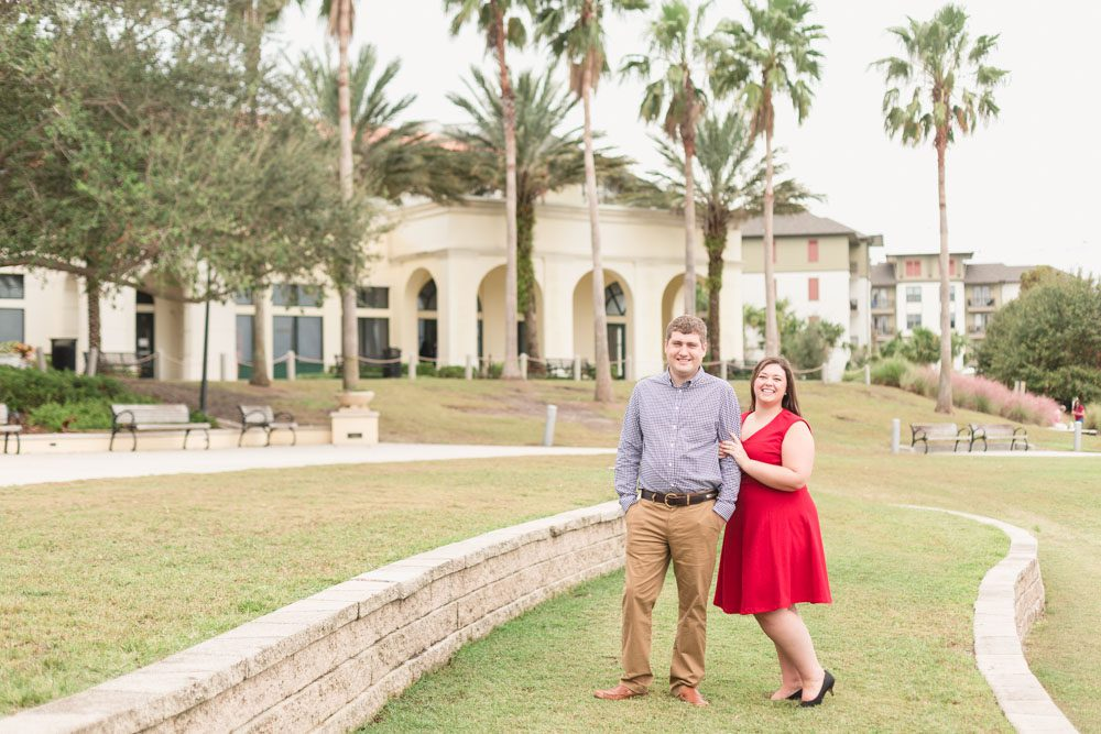 Beautiful engagement session with palm trees at Baldwin Park with the future bride wearing a beautiful red dress
