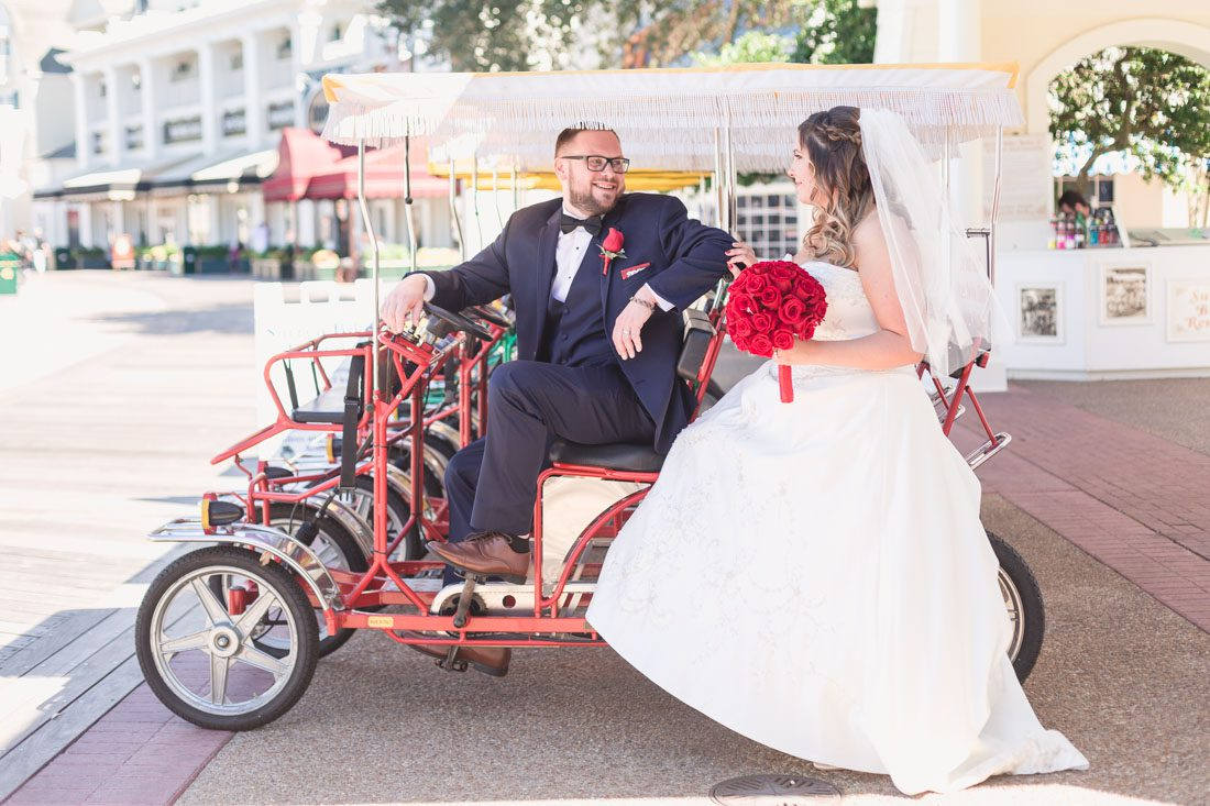 Photo of the bride and groom on a surrey bike at the Boardwalk Inn during their Disney wedding day