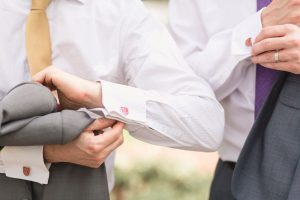 Groom and groomsman display their cuff links during a Disney themed elopement at Cypress Grove in Orlando