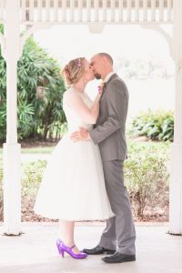 Newlyweds share their first kiss during their ceremony at Cypress Grove by top Orlando wedding photographers