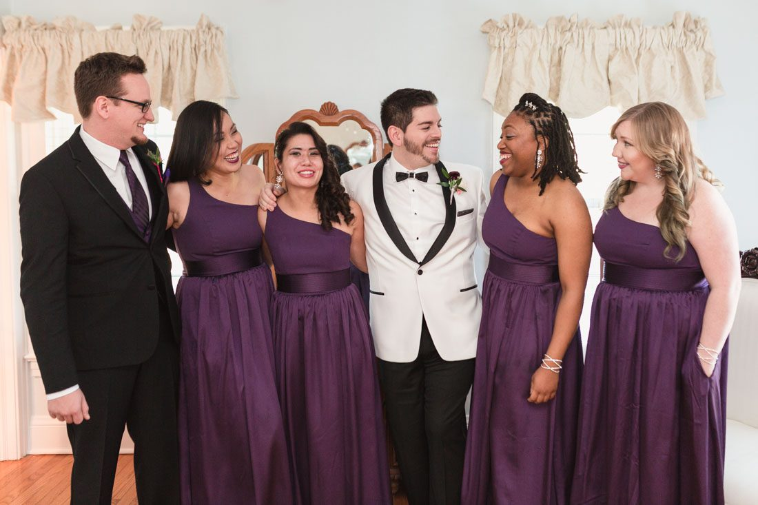 Photo of the wedding party wearing deep purple plum dresses at a gay Cypress Grove Estate House wedding in Orlando Florida