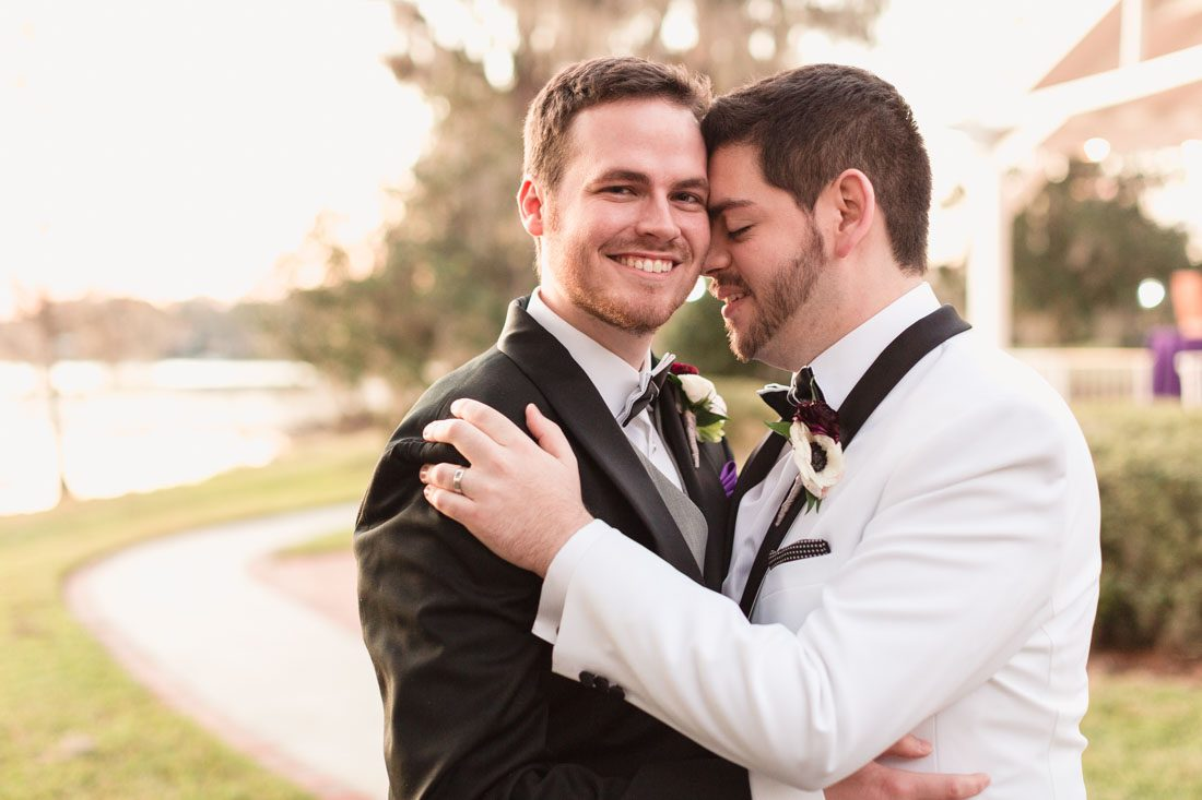 Portrait of two grooms at their gay wedding at sunset by the water in Orlando Florida
