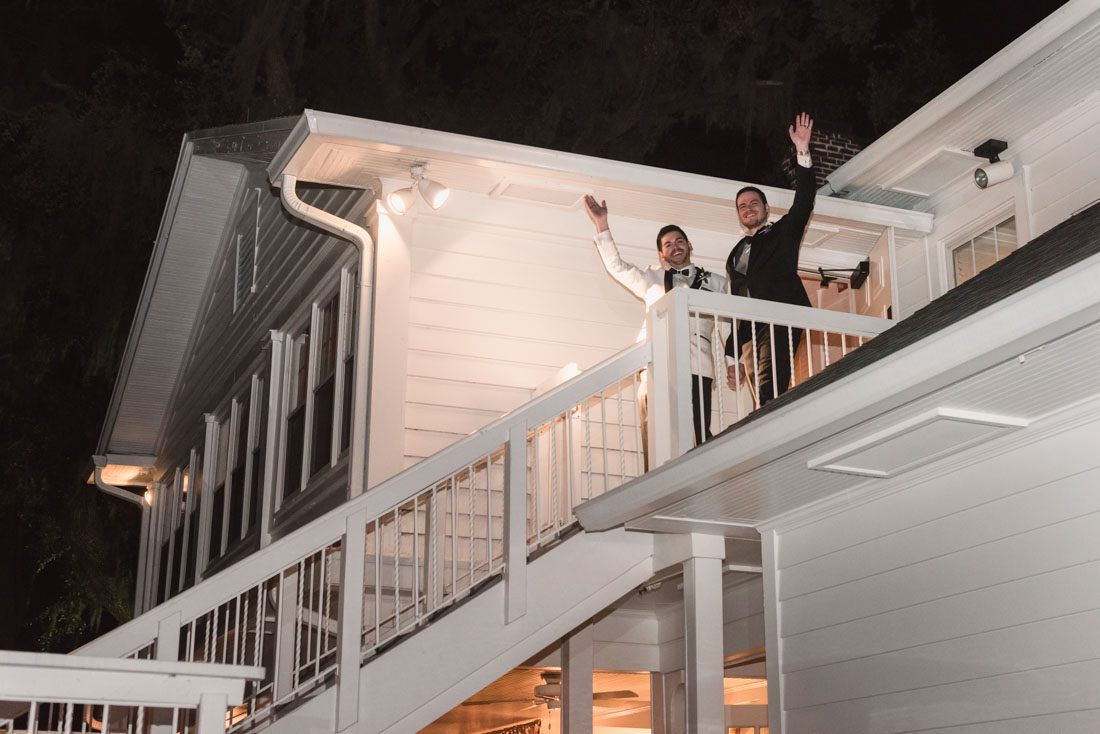 Grooms making their grand entrance from the balcony at their gay wedding in Orlando at Cypress Grove Estate House