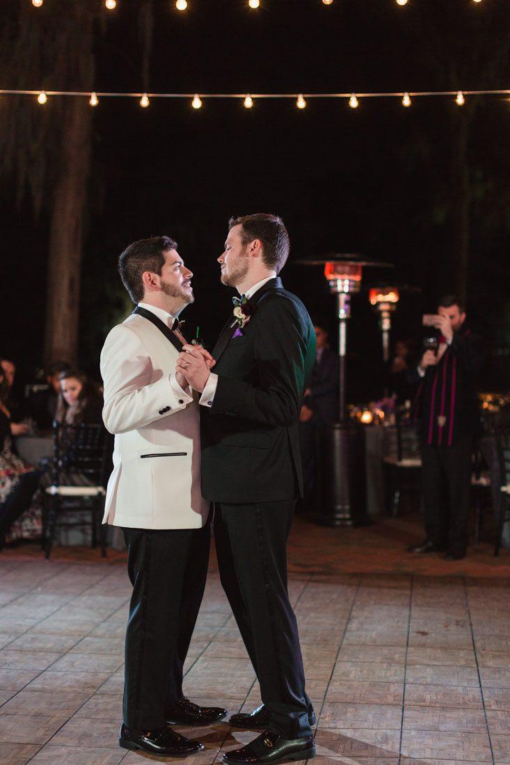Gay grooms share their first dance outdoors during their reception at Cypress Grove Estate House in Orlando