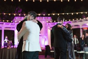 Candid photo during a gay Orlando wedding with the grooms sharing their first dance together at an outdoor venue in Orlando