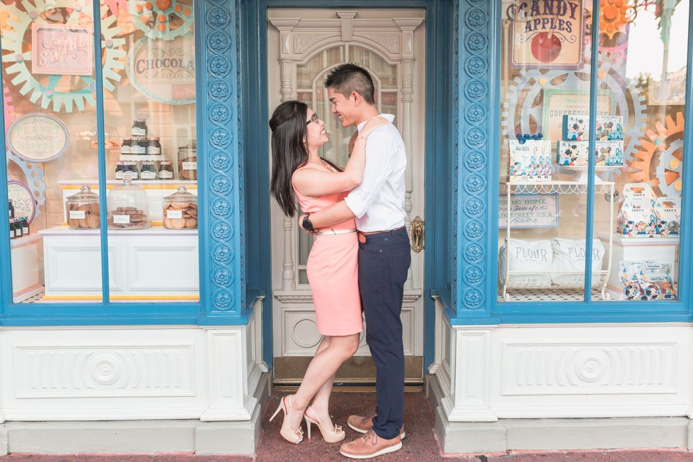 Disney engagement photography in front of the candy shop at Main Street at Magic Kingdom park in Orlando, Florida