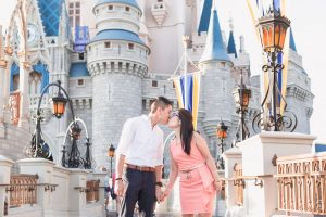 Engaged couple walking along Cinderella's castle at Walt Disney World park in Magic Kingdom during their engagement photography session in Orlando