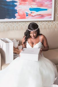 Bride opening her Jimmy Choo gift from her groom at the Four Seasons captured by wedding photographers in Orlando