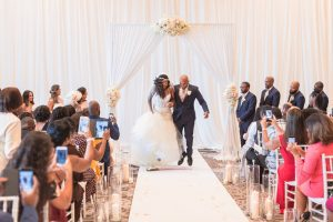 Newlyweds jump the broom as husband and wife during their indoor wedding ceremony in Orlando at the Four Seasons