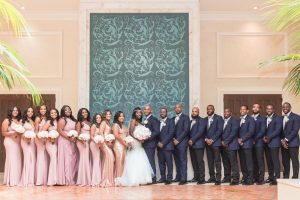 Photo of the entire bridal party featuring bridesmaids in pink and sequin dresses and groomsmen in blue suits at the Four Seasons