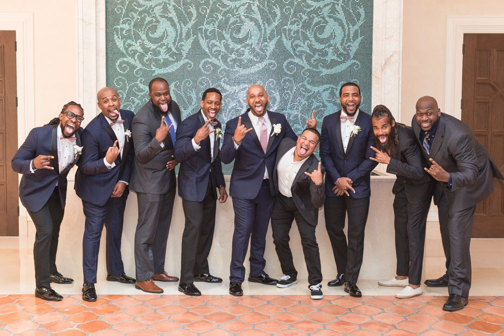 Groom poses for a fun photo with his fraternity brothers at the Four Seasons in Orlando