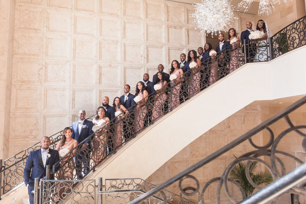 Bridal party portrait on the iconic steps of the Four Seasons in Orlando captured by top wedding photographer in Orlando