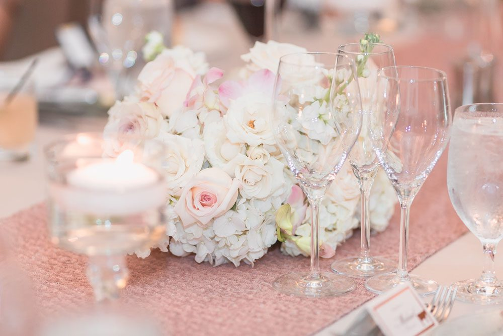 Reception ballroom for a Four Seasons wedding day featuring clear chairs and white, ivory and blush pink decor in Orlando