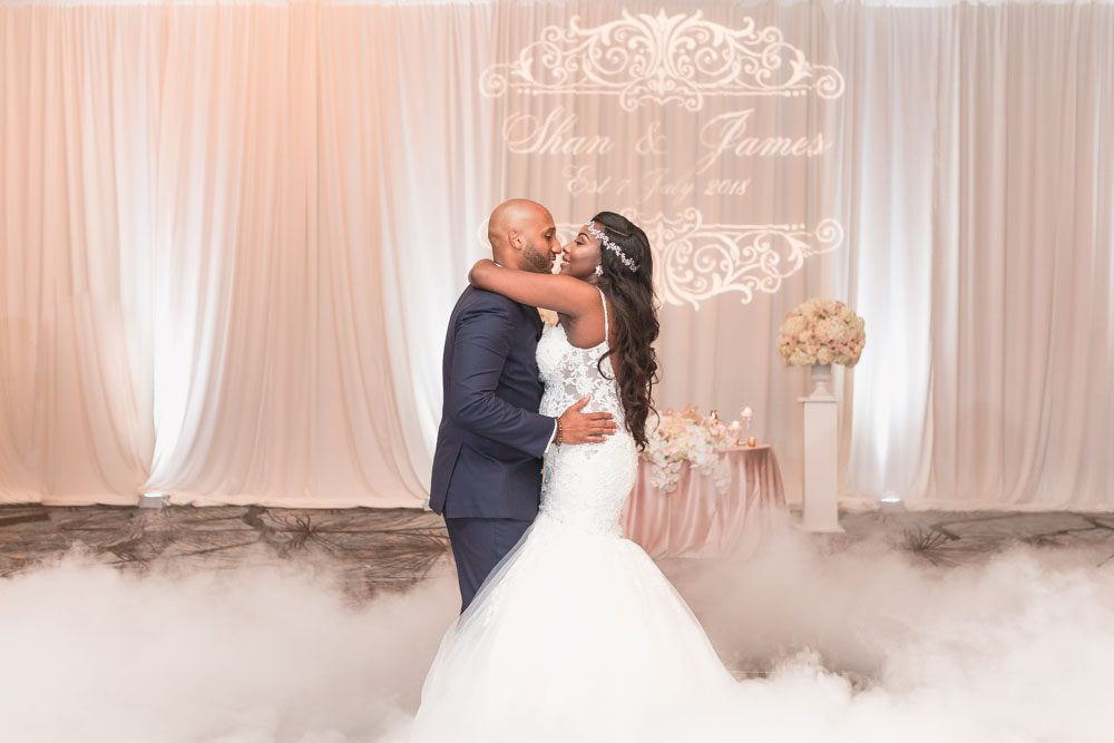 Bride and groom share their first dance on a cloud captured by top Orlando wedding photographer at their Four Seasons reception