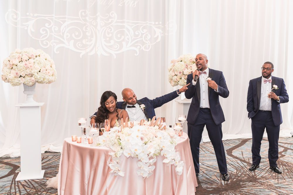 Bride and groom receive a toast from their best man and maid of honor at their reception at the Four Seasons resort in Orlando