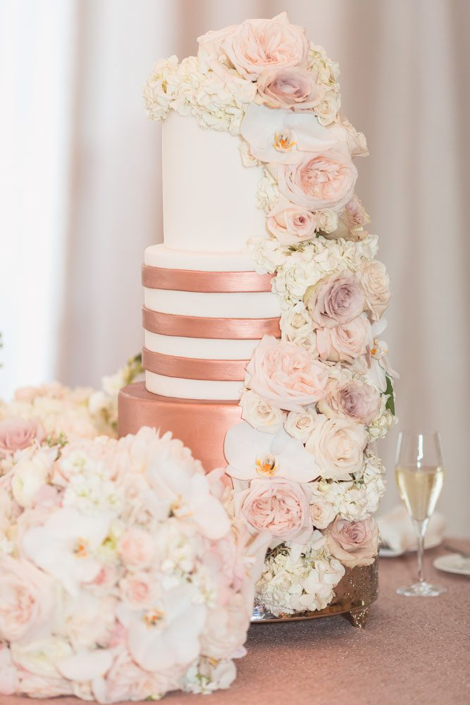 Orlando wedding photographer captures close up photo of gold and white wedding cake with flowers at the Four Seasons