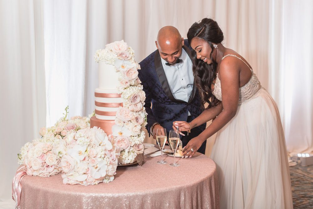 Orlando wedding photographer captures couple cutting of gold and white wedding cake with flowers at the Four Seasons
