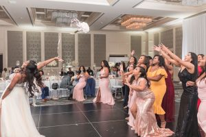 Orlando wedding photographer captures the bride as she throws her bouquet during her wedding reception at the Four Seasons