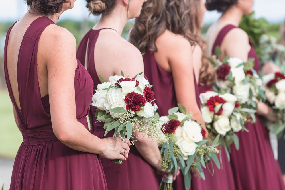 Orlando wedding photographer captures outdoor ceremony featuring burgundy red dresses and wine colored floral bouquets