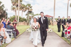 Outdoor wedding ceremony under a greenery arch at the Estate on the Halifax in Port Orange captured by Orlando wedding photographer