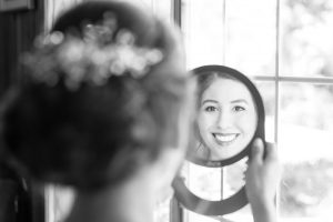 Bride looking at herself in the mirror during her wedding at the Estate on the Halifax east of Orlando, Florida