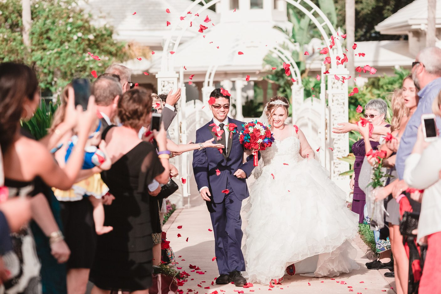 Grand exit with rose petals at Disney's wedding pavilion by Orlando wedding photographer