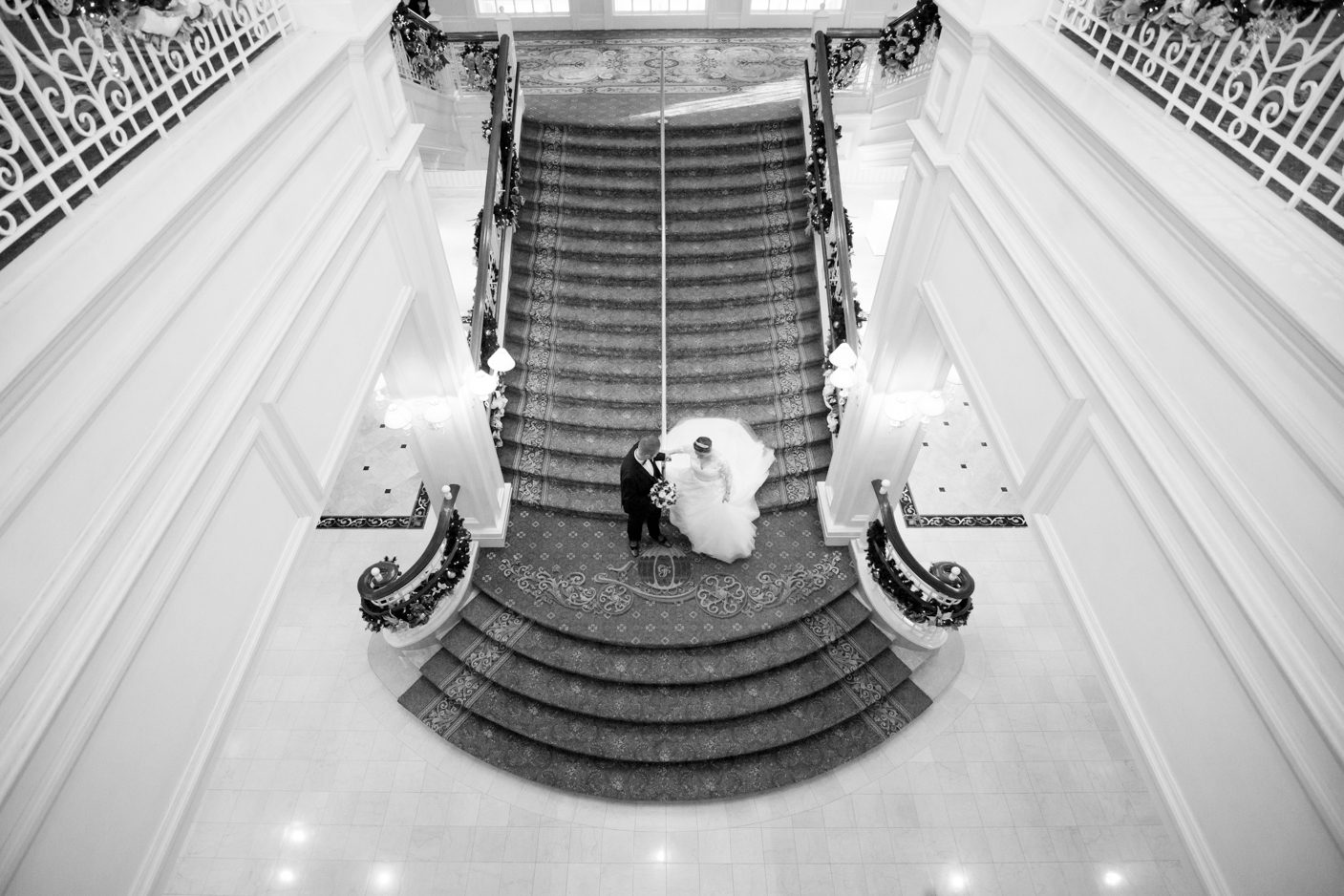 Black and white portrait of bride and groom at the grand staircase in the Grand Floridian during a disney wedding in Orlando