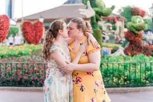 Brides kiss in Epcot during their same sex engagement photography session with top Orlando gay wedding photographer