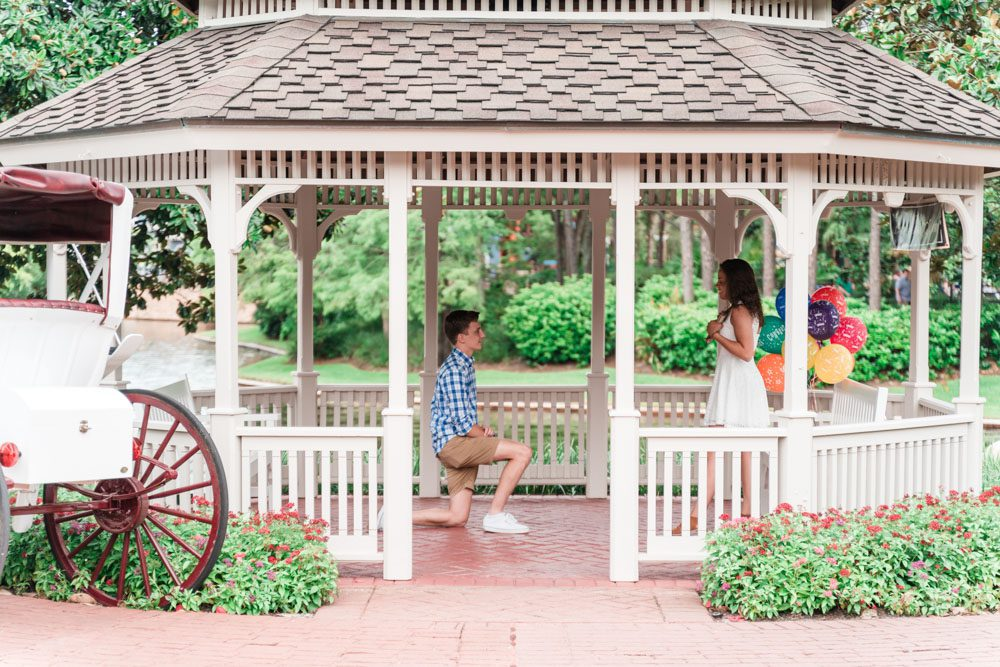 Surprise proposal photography at a gazebo at a Disney resort captured by top Orlando engagement photographer