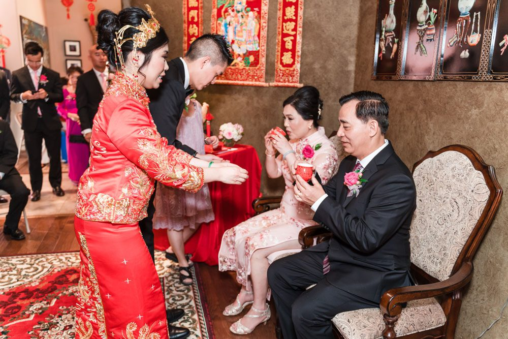 Bride and groom present tea during the traditional Asian ceremony on their wedding day captured by Orlando wedding photographers