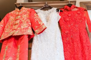 Traditional chinese and vietnamese red dresses hung alongside white wedding dress during an Asian wedding in Oklahoma City captured by Orlando wedding photographer