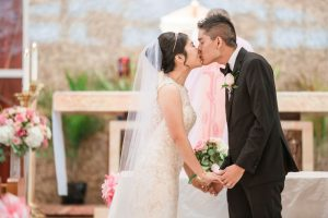 Asian bride and groom share their first kiss during their Catholic wedding ceremony in Oklahoma City