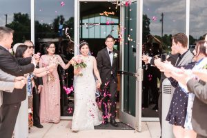 Bride and groom have their grand exit with confetti as they leave the church in Oklahoma City captured by top Orlando wedding photographers