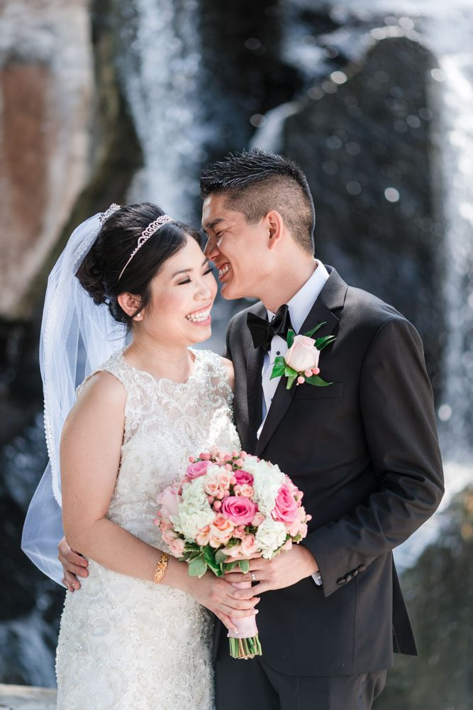 Candid portrait of the bride and groom at Myriad Gardens in front of a waterfall in Oklahoma City captured by traveling photographers from Orlando